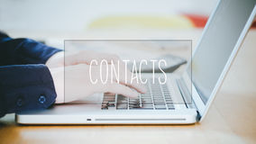 Contactos, texto sobre el hombre joven que mecanografía en el ordenador portátil en el escritorio foto de archivo libre de regalías