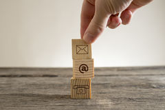 Contacts conceptual figure. Hand placing little wooden cube on stack over table with email and phone pictograms, business contacts conceptual figure Royalty Free Stock Photos