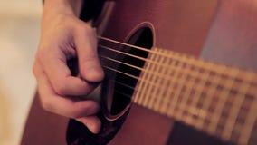 Contacts de la main de l'homme sur des ficelles de guitare acoustique par le médiateur Fin vers le haut banque de vidéos