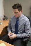 Contador Checking Phone no trabalho Foto de Stock