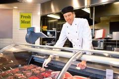 Contador de carne fresca con el carnicero Imágenes de archivo libres de regalías
