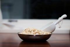 Contador de cozinha com farinha de aveia e copo Imagens de Stock