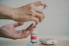 Contador de glucosa de sangre Ci?rrese para arriba de las manos de la mujer usando la lanceta fotografía de archivo