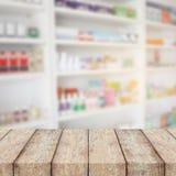 Contador de madeira com as prateleiras do borrão da droga na farmácia Imagem de Stock Royalty Free
