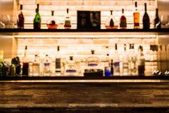 Contador de madeira escuro vazio da barra com as garrafas do fundo do borrão do re fotografia de stock royalty free