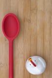 Contador de tiempo del pollo con la cuchara roja en el fondo de madera Fotos de archivo