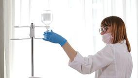 Contador del dropper con la clínica moderna de la medicación, enfermera de sexo femenino que ajusta el goteo intravenoso en la su almacen de metraje de vídeo
