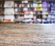 Contador do tampo da mesa com fundo borrado da livraria da estante fotografia de stock