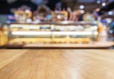 Contador do tampo da mesa com a loja borrada da padaria da prateleira de exposição Fotos de Stock Royalty Free