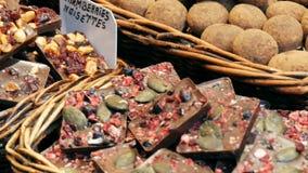 Contador grande con los diversos dulces redondos del chocolate en el esmalte con las nueces Barras de chocolate en el contador El metrajes