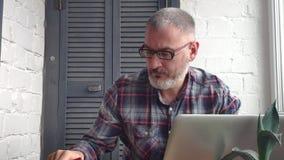 Contador masculino farpado grisalho que trabalha em casa atrás de um portátil, fazendo um relatório contra o contexto de um inter filme