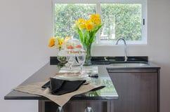 Contador negro en despensa con el florero de la planta y del fregadero moderno Foto de archivo