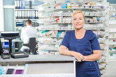 Contador sonriente de Leaning At Cash del farmacéutico adentro Fotografía de archivo