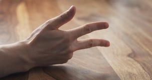 Contagem do dedo da mão do homem novo na tabela Fotografia de Stock