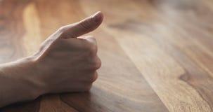 Contagem do dedo da mão do homem novo na tabela Fotos de Stock