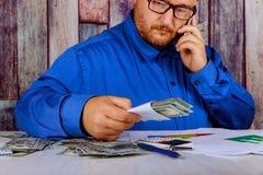 A contagem do neg?cio desconta d?lares americanos acima no telefone celular do homem das m?os no dinheiro fotos de stock royalty free