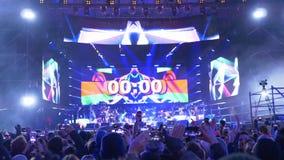 Contagem regressiva de Digitas ao começo do concerto na fase que olha uma multidão emocional de povos com os telefones celulares  vídeos de arquivo