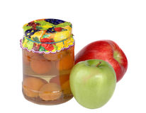 Container with apricot compote. Green and red apple on white background Stock Photos