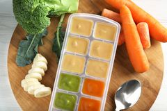 Container with baby food. On wooden board Stock Images
