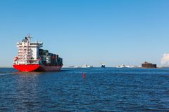 Container with cargo. At sea in clear weather against the dam and Fort Alexander on the island Kotlin Royalty Free Stock Photography