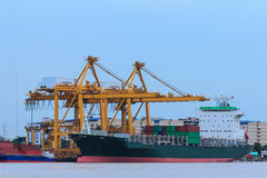 Container Cargo freight ship with working crane br Stock Photo