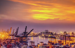 Container Cargo freight ship with working crane bridge in shipya. Rd at dusk for Logistic Import Export background Royalty Free Stock Photo