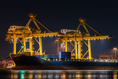 Container cargo freight ship with working crane bridge in shipya. Rd at night for logistic import export Royalty Free Stock Photography