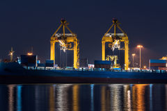 Container cargo freight ship with working crane bridge in shipya Stock Image