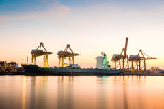 Container Cargo freight ship with working crane bridge in shipya Stock Photos