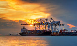 Container Cargo freight ship with working crane Stock Photography