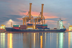 Container Cargo freight ship with working crane bridge in shipyard Stock Images