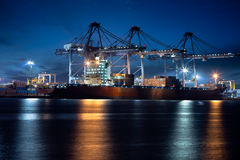 Container Cargo freight ship with working crane bridge in shipyard at dusk for Logistic Stock Photos