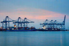 Container Cargo freight ship with working crane bridge in shipyard at dusk for Logistic Import Export Royalty Free Stock Photos