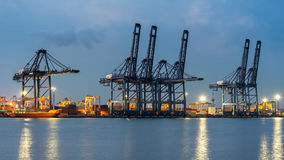 Container Cargo freight ship with working crane bridge in shipyard at dusk for Logistic Import Export background. Stock Photos