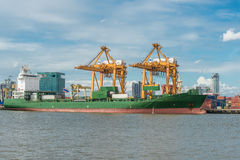 Container Cargo freight ship with working crane bridge Stock Photo
