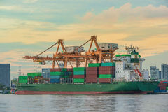 Container Cargo freight ship with working crane loading bridge i Royalty Free Stock Photos