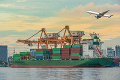 Container Cargo freight ship with working crane loading bridge i Royalty Free Stock Photography