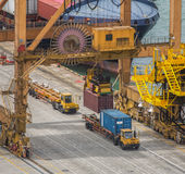 Container Cargo freight ship with working crane loading bridge i Stock Images