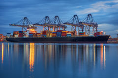Container Cargo freight ship with working crane loading Stock Photo