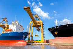 Container cargo freight ship with working crane loading bridge. In shipyard for logistic Import export background Stock Photo