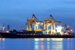 Container Cargo freight ship with working crane Stock Photo