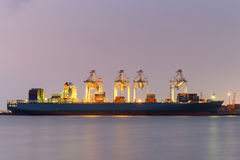 Container Cargo freight ship with working  Export at twilight Stock Image