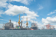 Container Cargo freight ship with working gantry in shipyard for Stock Image