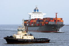 Container cargo ship with ocean tug Stock Images
