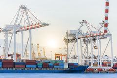 Container Cargo ship with ports crane bridge in harbor Royalty Free Stock Image