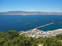 Container and cargo ships around the Rock of Gibraltar. With the port of Algeciras, Spain, in the background Royalty Free Stock Image