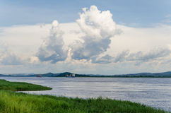 Container cargo ships on mighty Congo river with dramatic sky. Container cargo ships on mighty Congo river with dramatic cloudy sky and lush green grass in Royalty Free Stock Photo
