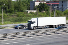 Container chassis truck driving on highway near cars Royalty Free Stock Photos