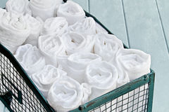 Container of Cleaning Rags. Pretty green basket filled with neatly organized rolled up cleaning rags. Shallow depth of field Royalty Free Stock Image