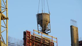 Container with concrete delivered by crane on building site, construction works. Stock photo stock images